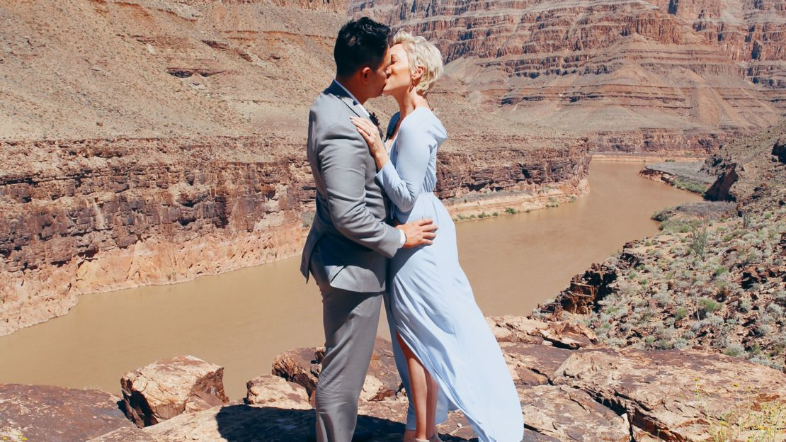 Bride and groom kissing after vows in front of Colorado River in Grand Canyon.