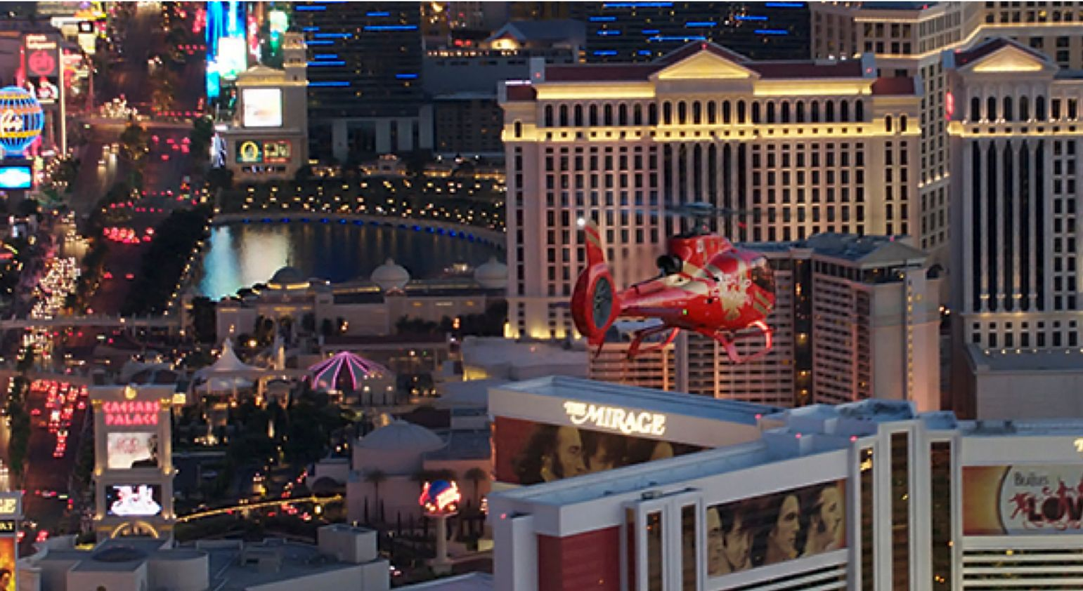 Helicopter flying over Las Vegas Strip at night.