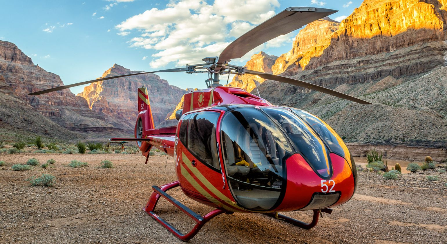 The Grand Canyon floor with a red helicopter landed in the foreground.