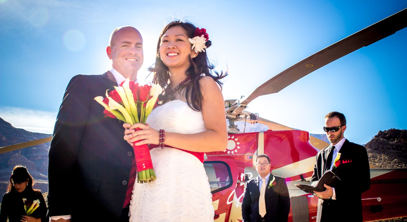 A bride and groom stand in front of a helicopter at their Grand Canyon wedding.