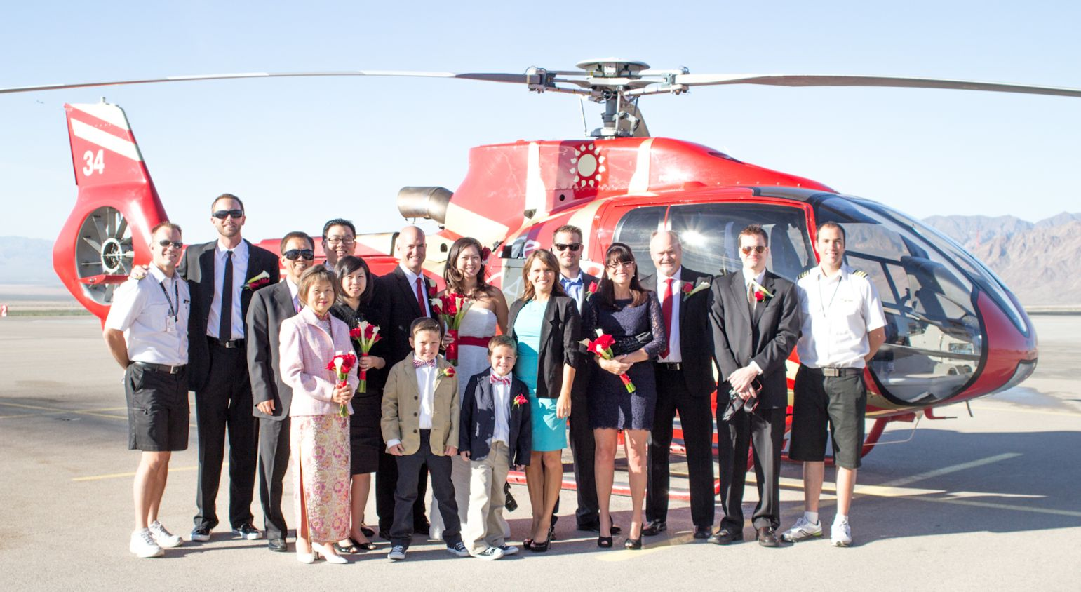A small wedding group poses in from of a Grand Canyon helicopter.