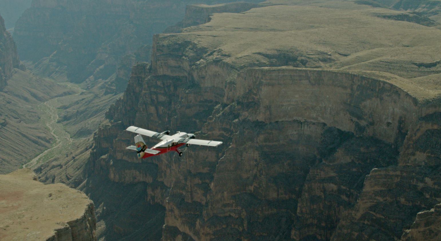 A red and white helicopter flies over a huge stone gorge within the Grand Canyon West.