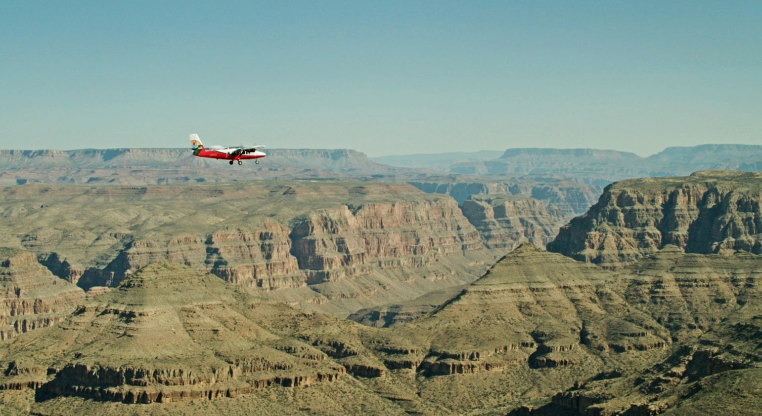A small red and white airplane soars over a stone gorge of the Grand Canyon National Park.