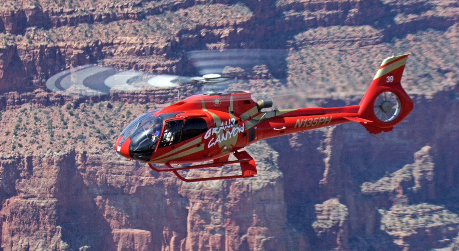 A red helicopter, central in the image, flies through the walls of the Grand Canyon.