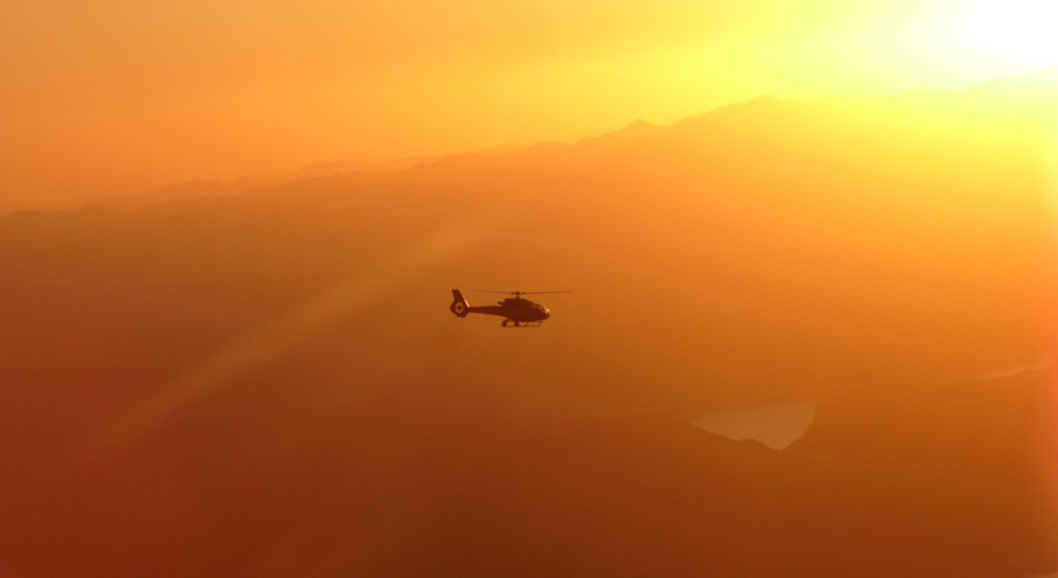 A helicopter flies in an orange sky at sunset.
