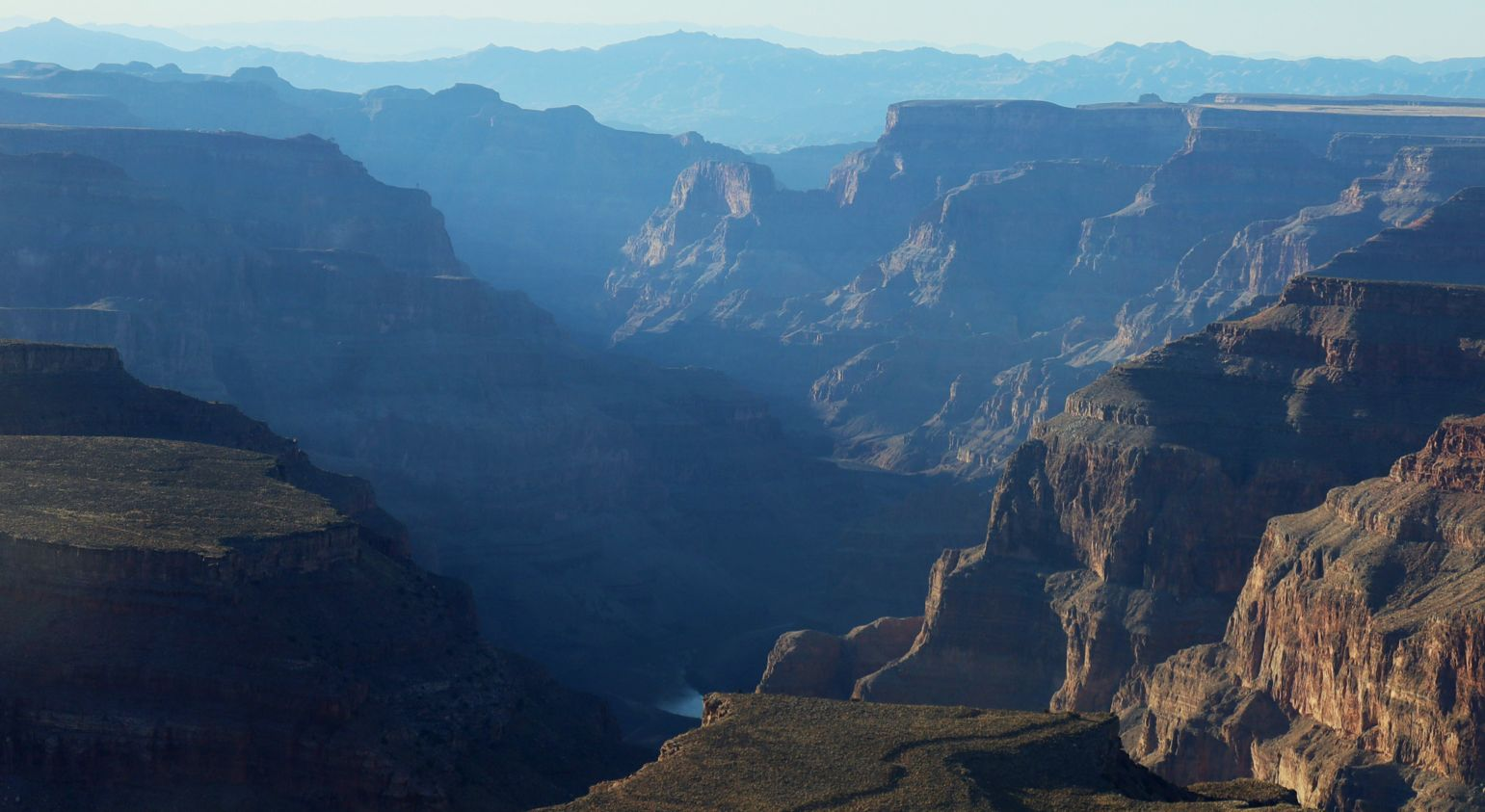 Warm sunny weather creates a bluish mist over the walls of the Grand Canyon West.