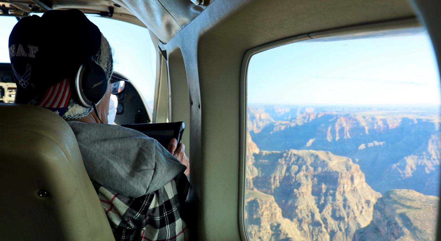 A man aboard a Grand Canyon airplane tour takes a photo of the landscape through his window using his phone.