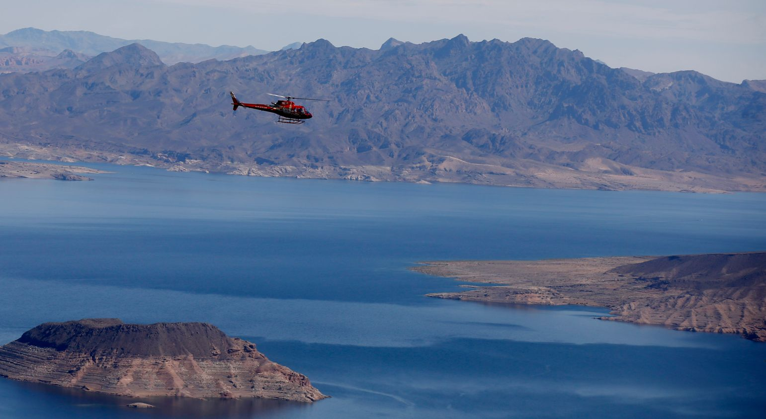 A red helicopter flies over Lake Mead en route to a Grand Canyon tour.