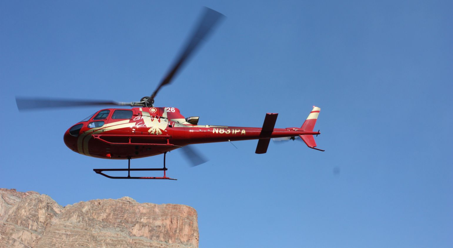 A red A-Star flies on a Grand Canyon helicopter tour.