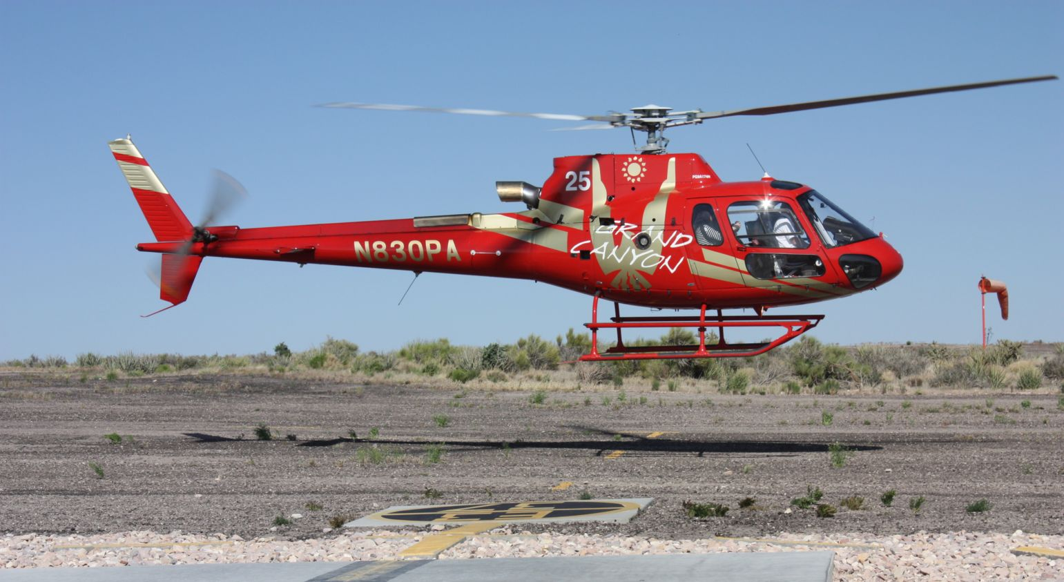 A red helicopter lands at the Grand Canyon West Rim.