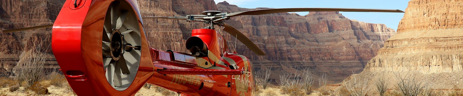 Red EC130 Helicopter landed at the bottom of the canyon on a sunny day at Grand Canyon West on the West Rim Motorcoach with Heli, Boat, and Skywalk Tour
