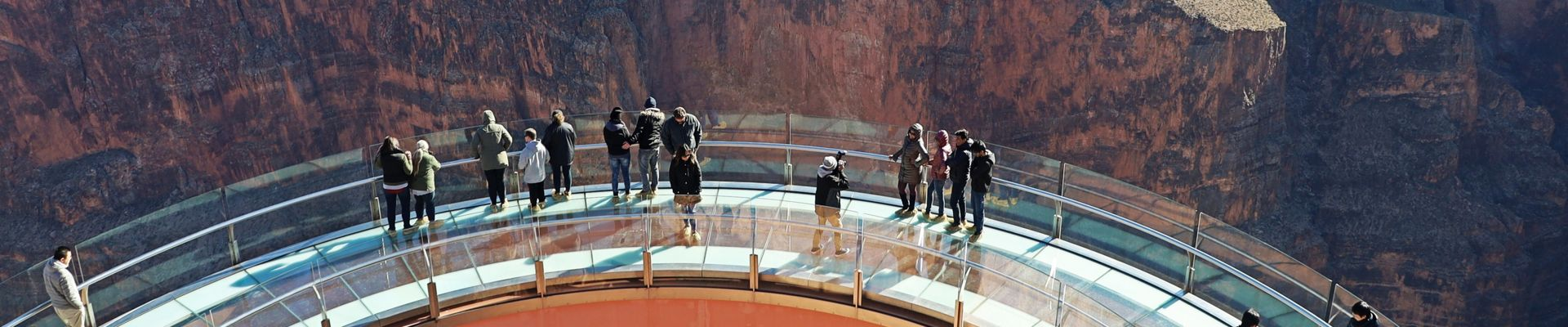 View of the Grand Canyon Skywalk from above with people enjoying the views of Grand Canyon West Rim on a bright sunny day on the Grand Voyager with Skywalk Tour