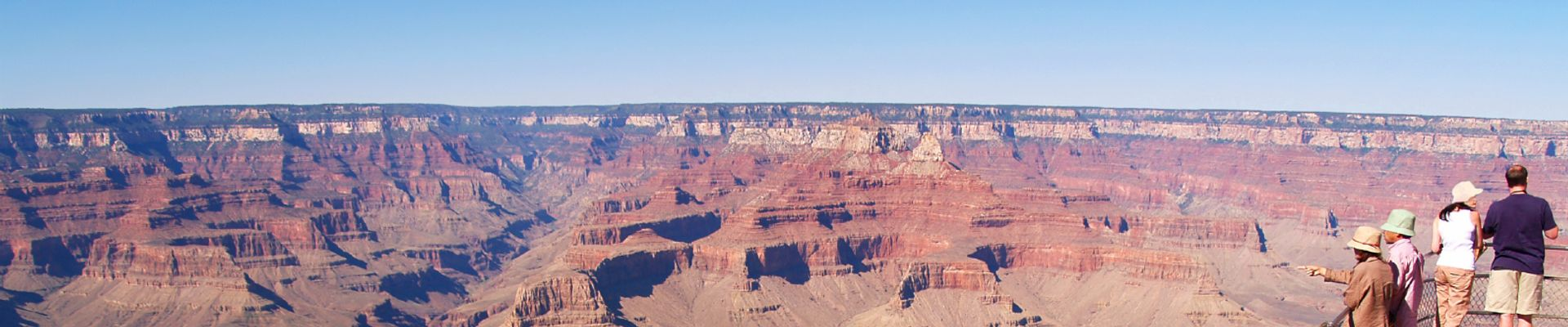 A group of sightseers stand at the edge of the Grand Canyon National Park.