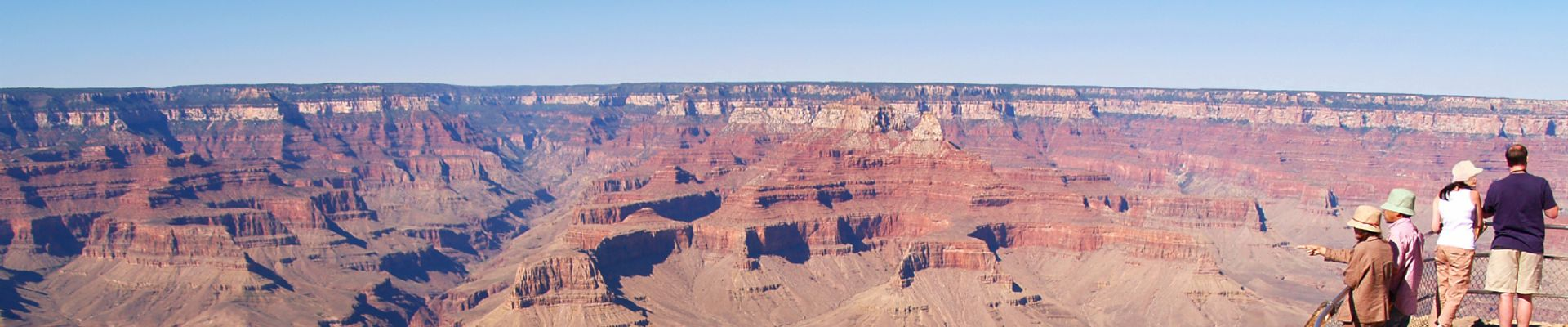 Visitors to the Grand Canyon National Park stand near the edge of a beautiful canyon lookout point.