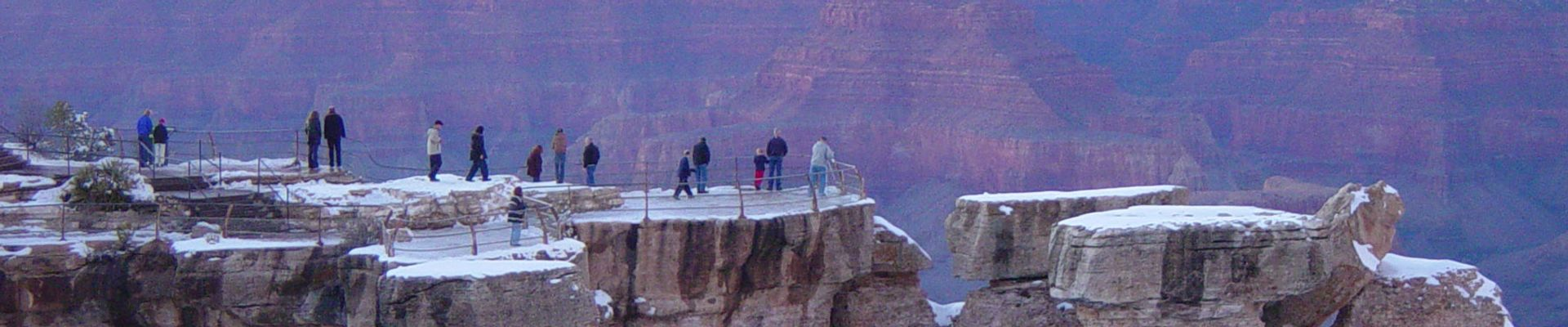 A man takes a photo of a sunset at the Grand Canyon.
