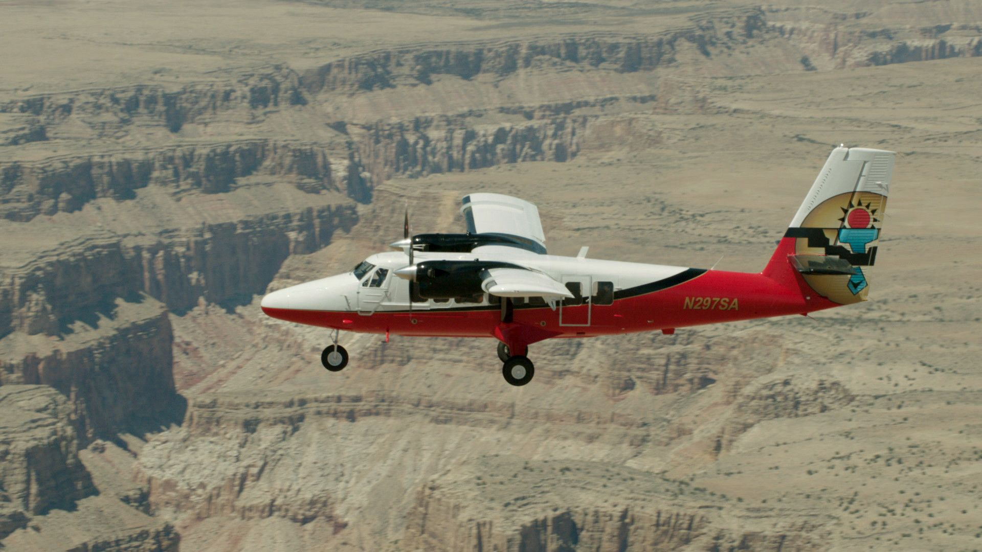 Twin otter airplane flying above the desert landscape of the grand canyon
