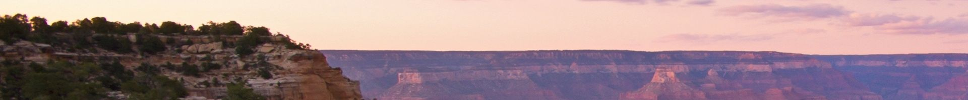 The Grand Canyon National Park with pink light from the sunset scattered across the stone walls.