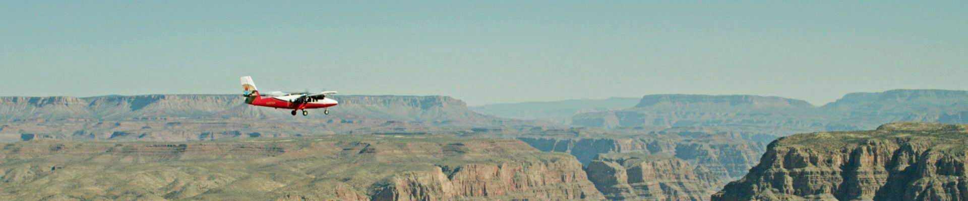 A small aircraft flies over a wide Grand Canyon landscape.