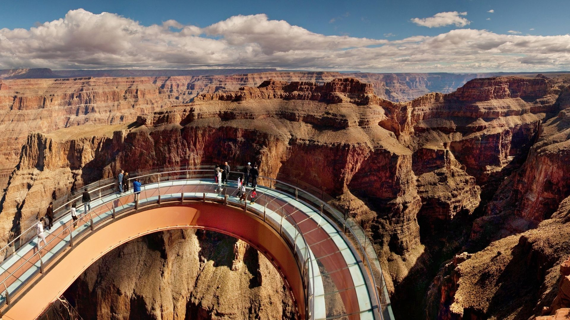 Guests standing on a steel and glass arch, far above the canyon floor. Eagle Point is behind them.