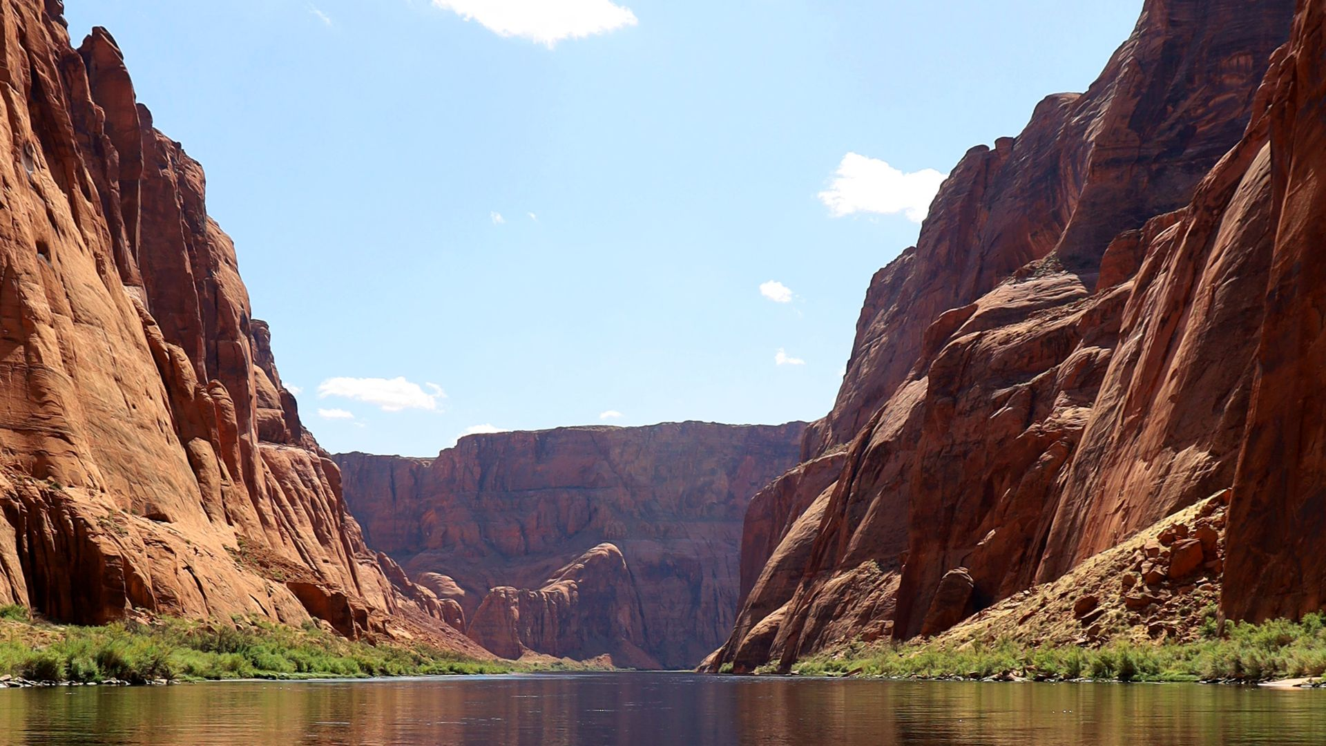 Standing in the middle of the Colorado River looking down-canyon with red rock rising on both sides
