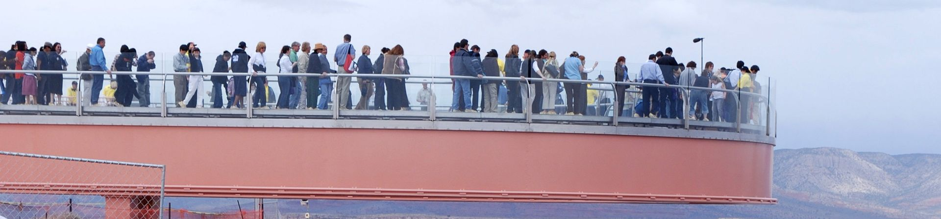 A large group of visitors to the Grand Canyon West Rim stand atop the Skywalk Bridge.