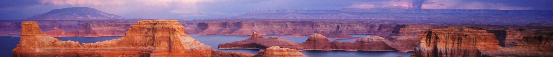 A scenic expanse of Lake Powell's blue waters as well as orange rock formations surrounding them.