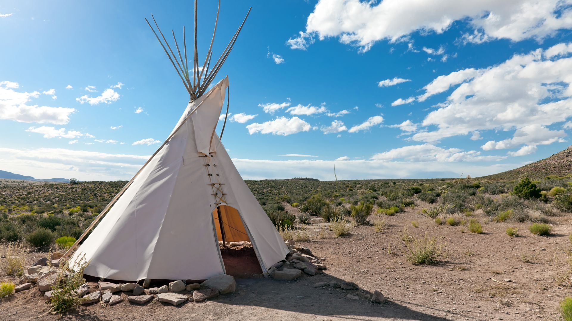 A traditional Tipi, sitting among a green desert landscape at Hualapai Ranch