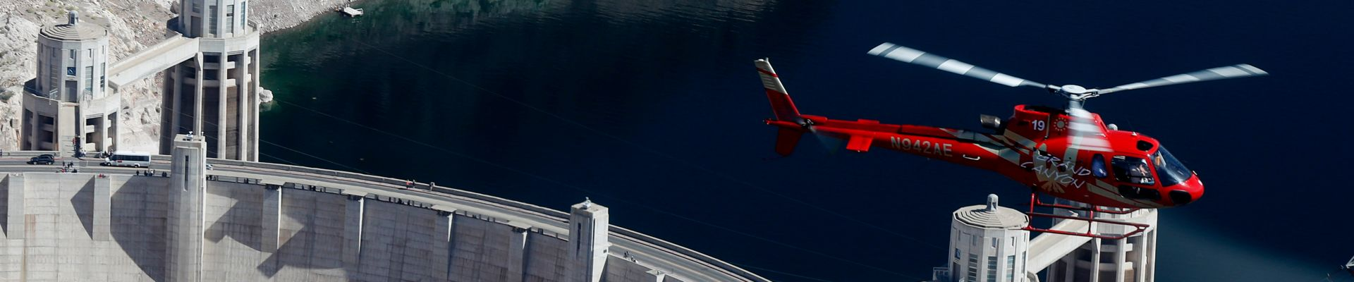 A red AStar Helicopter flying over the Hoover Dam, dark blue waters below.