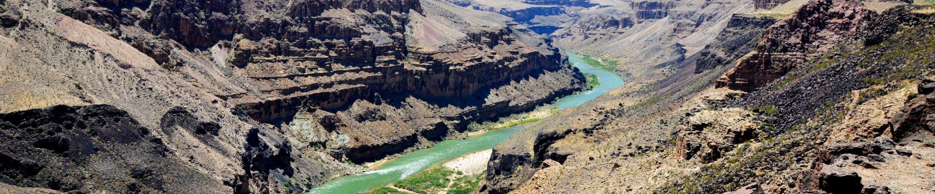 The blue Colorado River cuts through stark Grand Canyon walls.
