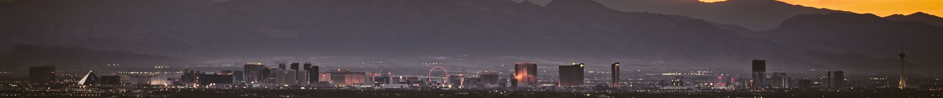 The Las Vegas Strip skyline seen at sunset with mountains deep in the background.