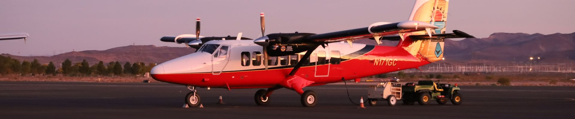 A Twin Otter airplane parked on an airport tarmac at sunset.