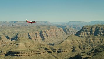 Twin Otter airplane flying over the Grand Canyon on a hazy day