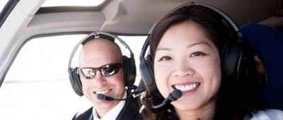 Two passengers smile aboard a Papillon Grand Canyon helicopter tour.