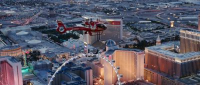 A Las Vegas helicopter tour flies over the Strip casinos and a Ferris wheel.