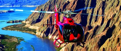 A red helicopter flies through the walls of the Grand Canyon above the Colorado River.