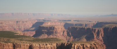 The Grand Canyon seen in sunny weather with a misty fog over the stone walls.