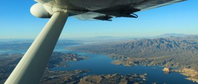 An airplane tour from Las Vegas flies over the blue waters of Lake Mead and the surrounding nature.