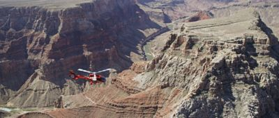 A red helicopter flies over a massive Grand Canyon landscape.