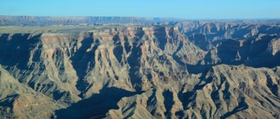 A sunny landscape of the Grand Canyon West with a clear blue sky above.