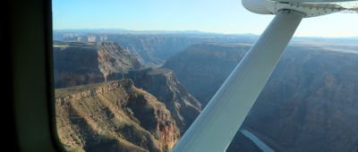 A view of the Grand Canyon West Rim seen through the window from inside a Grand Canyon airplane tour.