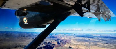 The Grand Canyon seen from the window of an airplane tour, with the plane's wing prominent in the photo.