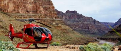 A red helicopter rests on the floor of the Grand Canyon, visible in the background along with the Colorado River.