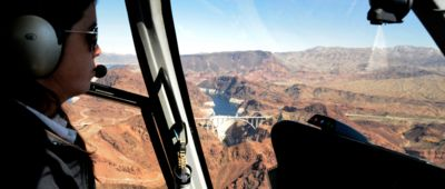 A view of the Hoover Dam seen from inside a helicopter tour, with a female pilot seated to the left.
