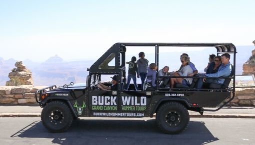 Guests on a Buck Wild branded Hummer in front of the Grand Canyon South Rim.