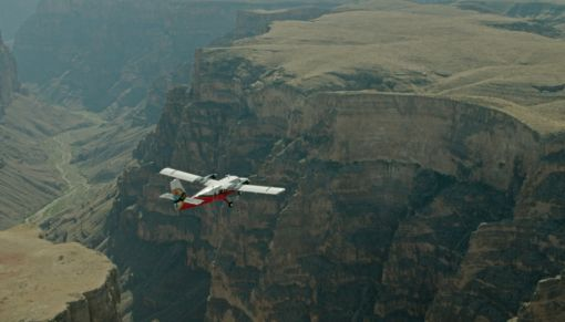 A red and White Airplane Flying over a green desert landscape