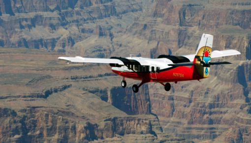 A red and white airplane flying over the Grand Canyon