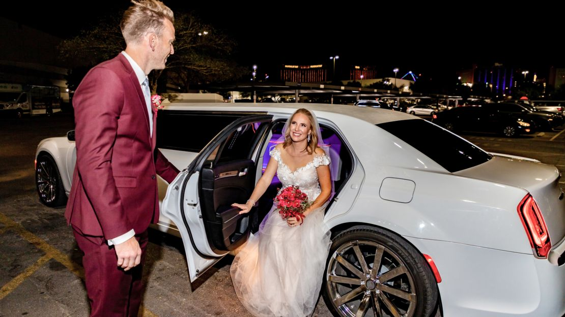 Groom holding open door for Bride as she gets out of the luxury limousine.