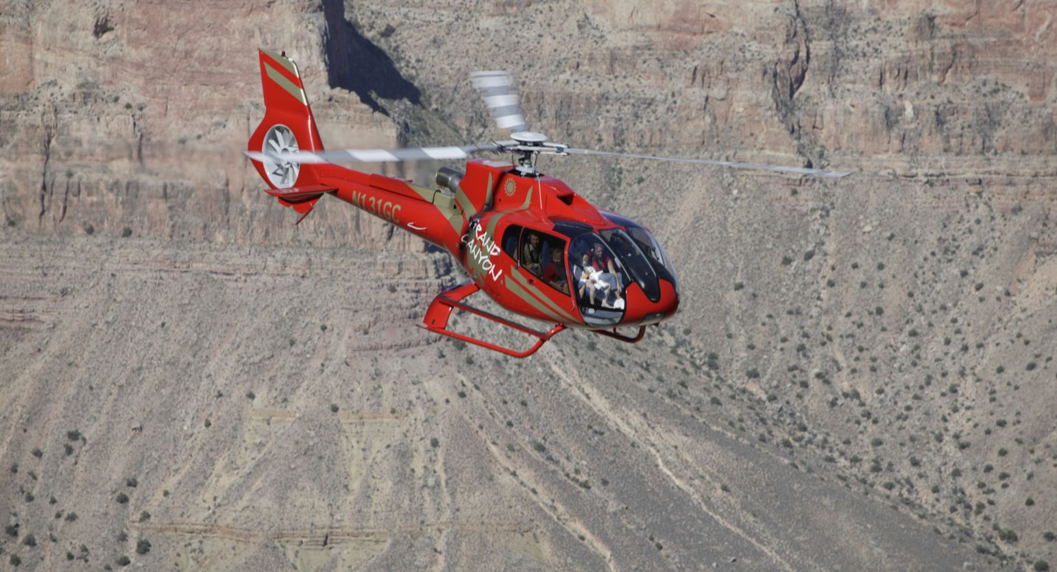 Red EC130 flying over the east rim of the Grand Canyon