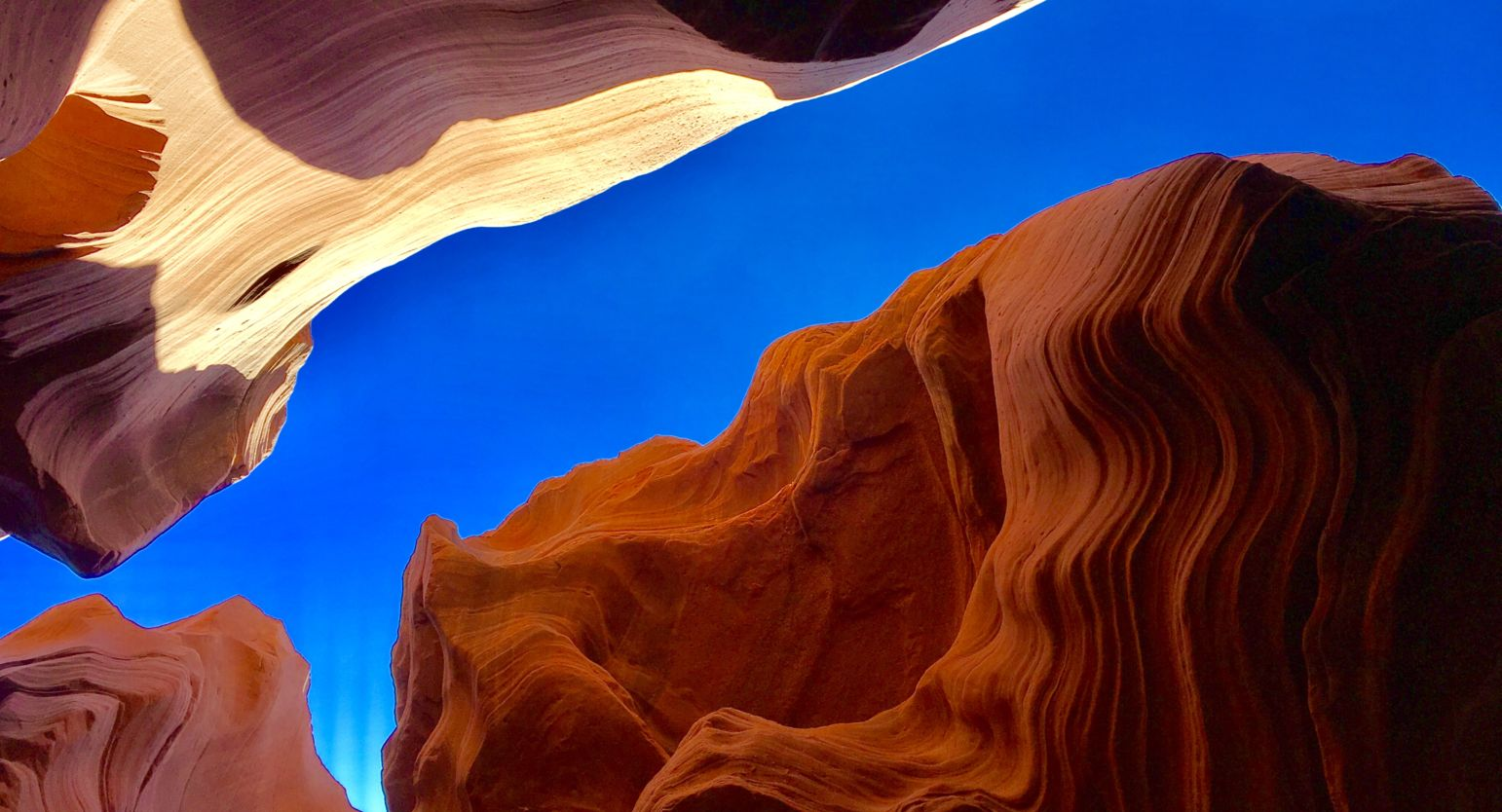 View of the crystal blue sky looking up from the inside of Antelope Canyon