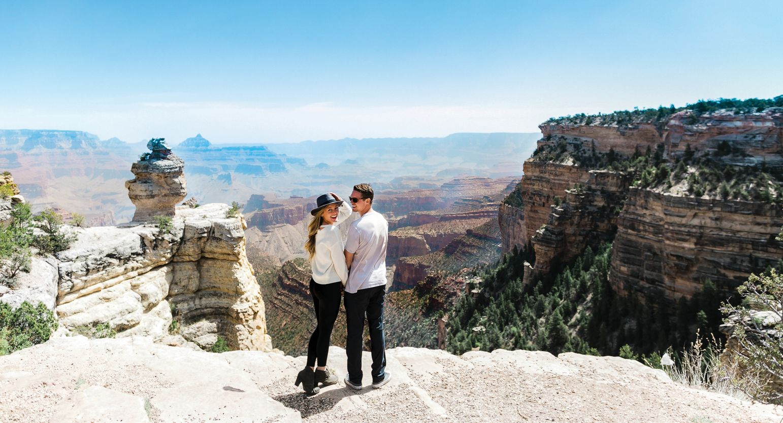 Couple holding hands standing near the edge of the Grand Canyon.